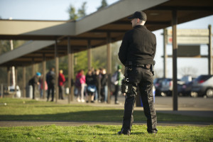 Armed security guard James Mortenson, from Phoenix Protective Corporation, patrols Ridgefield High School as students are released for the day, Thursday, January 17, 2013. (Steven Lane/The Columbian)